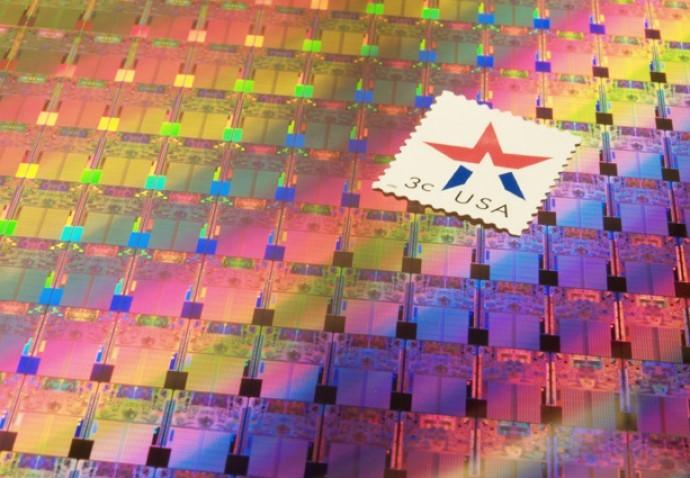 Un wafer di chip a 45 nm a confronto con un francobollo delle poste USA